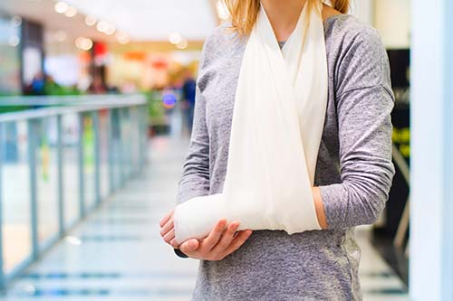 Woman in an arm sling with a personal injury